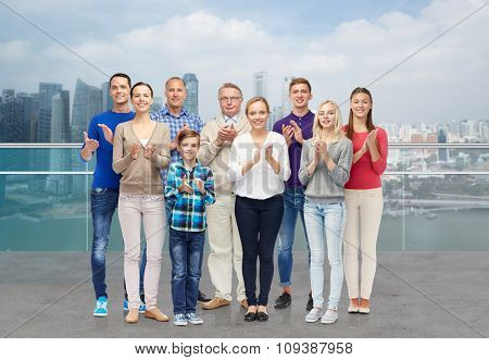 family, gender, generation and people concept - group of smiling men, women and boy applauding over singapore city waterside background