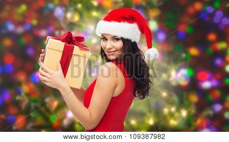 people, holidays, christmas and celebration concept - beautiful sexy woman in red dress and santa hat with gift box over party lights background