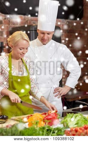 cooking class, culinary, food and people concept - happy male chef cook with woman cooking in kitchen over snow effect