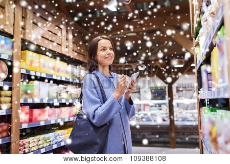 sale, shopping, consumerism and people concept - happy young woman taking notes to notebook in grocery store or market over snow effect