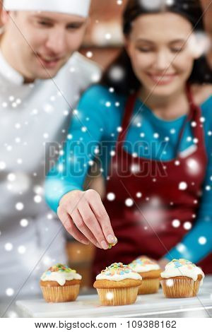 cooking class, culinary, bakery, food and people concept - happy group of woman and male chef cook baking in kitchen over snow effect
