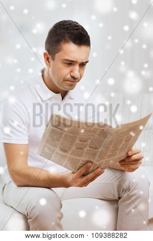 leisure, information, people and mass media concept - sad man reading newspaper at home with snow effect
