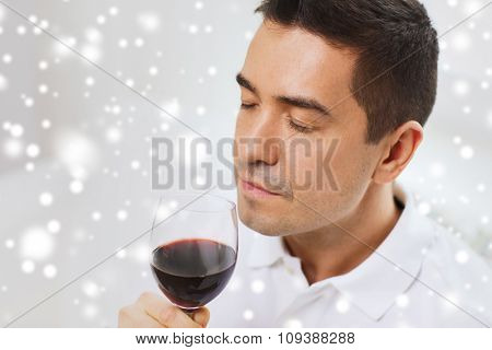 profession, drinks, leisure and people concept - happy man drinking and smelling red wine from glass over snow effect