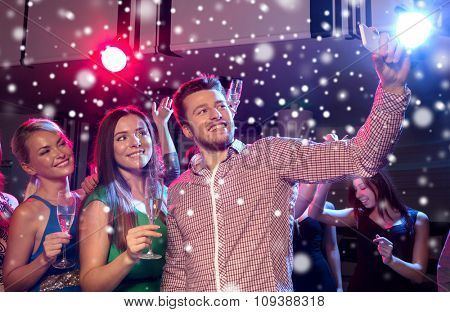 new year party, holidays, technology, nightlife and people concept - smiling friends with glasses of champagne and smartphone taking selfie in club and snow effect