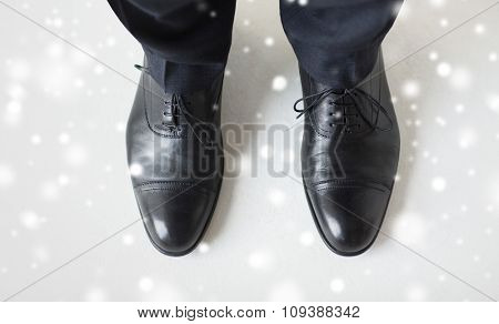 people, business, fashion and footwear concept - close up of man legs in elegant shoes with laces or lace boots over snow effect