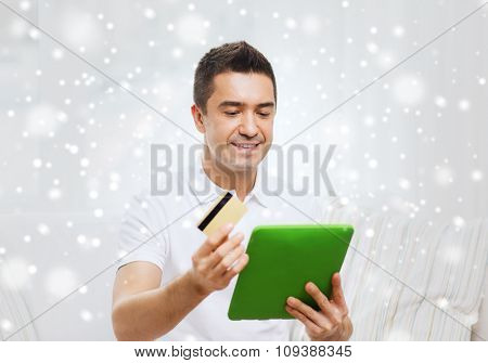 technology, people, online shopping and finances concept - happy man with tablet pc computer and credit card at home over snow effect