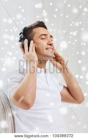 technology, people and lifestyle concept - happy man in headphones listening to music at home over snow effect