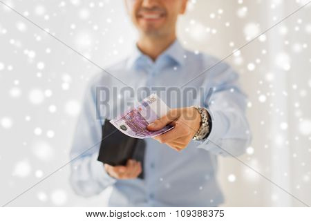 people, business, finances and money concept - close up of businessman hands holding open wallet with euro cash over snow effect