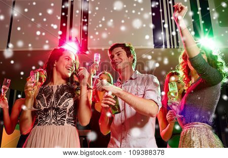new year party, holidays, celebration, nightlife and people concept - smiling friends clinking glasses of non-alcoholic champagne and beer in club and snow effect