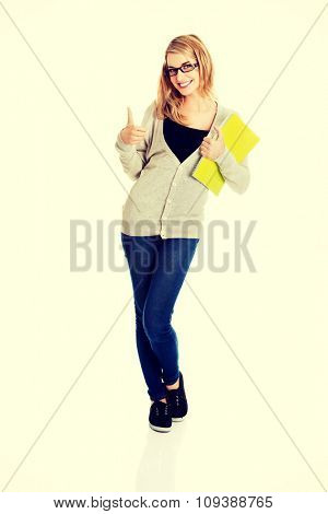 Young woman thumbs up, holding notes.