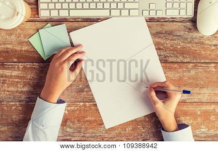 business, education, technology and people concept - close up of female hands with paper sheet, pencil and computer keyboard on table