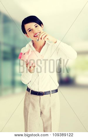 Happy businesswoman putting an euro coin into a piggy bank