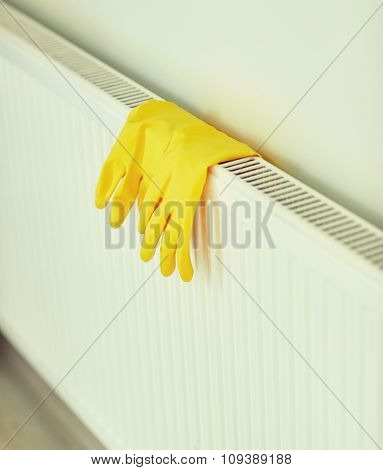 protection, housework and housekeeping concept - close up of yellow rubber gloves hanging on heater at home