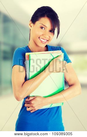 Happy student woman with notebooks.