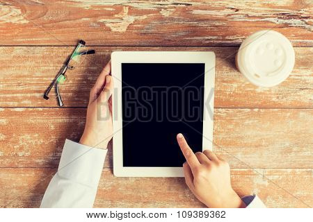 business, education, people and technology concept - close up of female hands pointing finger to tablet pc computer black blank screen with coffee cup and eyeglasses
