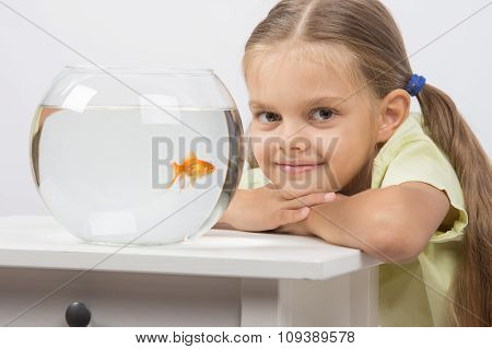 Six Year Old Girl Put Her Head On The Handle Sitting At The Table With An Aquarium With Goldfish