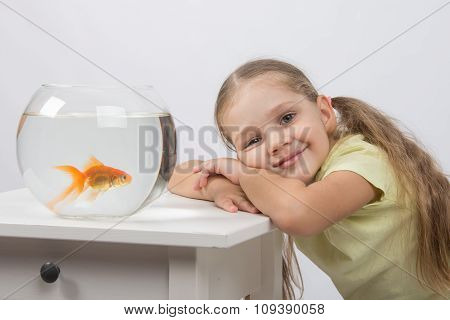 Happy Four-year Girl Put Her Head In His Hands Sitting In Front Of A Goldfish