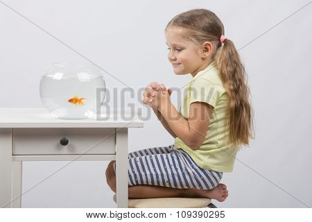 Four-year Girl Makes A Wish Sitting In Front Of A Goldfish
