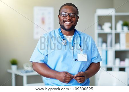 Happy doctor in uniform looking at camera in clinic
