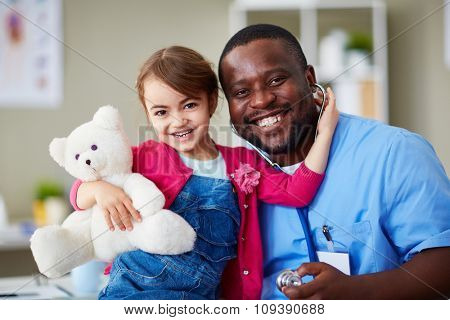 Joyful girl and her doctor looking at camera with smiles