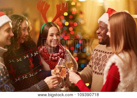 Happy friends toasting with bubbly champagne on Christmas eve