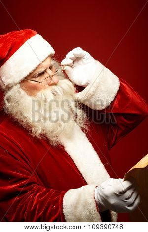 Santa Claus reading Christmas letter