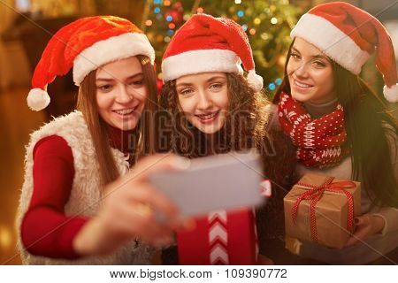 Happy girls in Santa caps making selfie at Christmas party