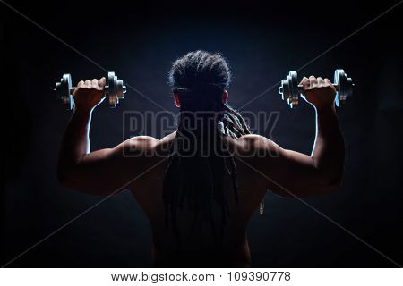 Back view of muscular man with dreadlocks training in gym
