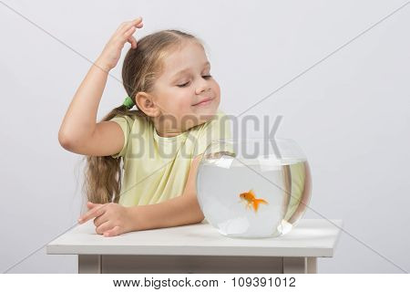 Four-year Girl Make A Wish While Enjoying A Goldfish In An Aquarium