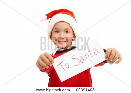 Happy boy in Santa cap showing Christmas letter