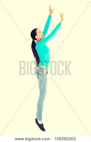 Full length woman trying to reach high.