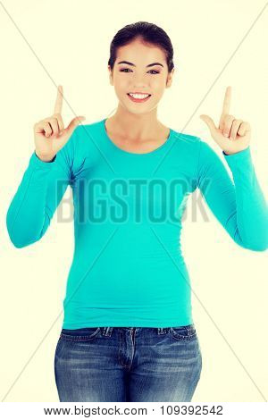 Full length woman pointing up.