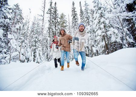 Happy young friends running in snowdrift