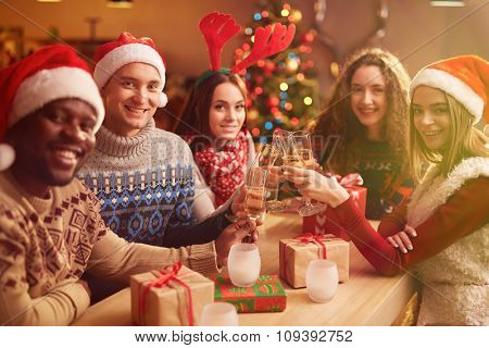 Happy guys and girls spending Christmas evening together
