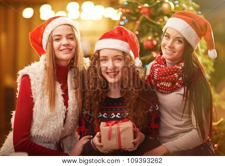 Happy girls in Santa caps looking at camera on Christmas evening