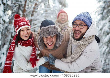 Happy friends having fun in park in winter