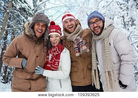 Young multi-ethnic friends in winterwear looking at camera outdoors