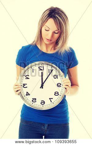 Full length woman holding big clock.
