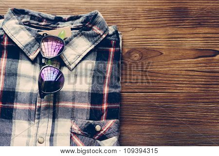 Men's Plaid Shirt And Colored Glasses On A Wooden Background
