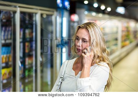 Blonde woman on a phone call in the supermarket