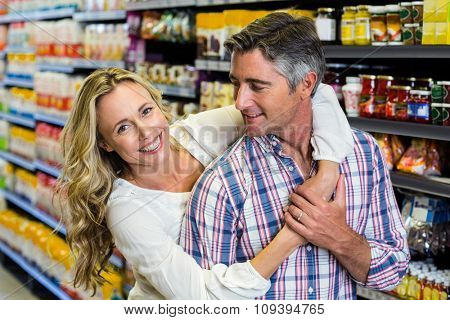 Happy couple hugging at supermarket