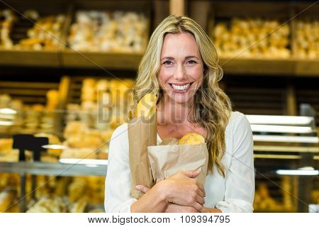 Beautiful woman holding paper bag with bread in supermarket