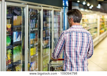 Back view of man holding cart in supermarket