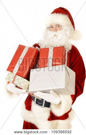 Portrait of a traditional Santa Claus holding gift boxes in his hands. Christmas. Isolated over white.