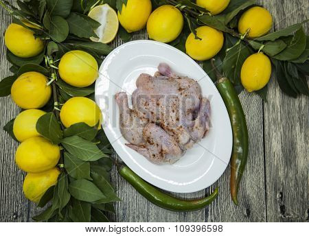 Raw fresh chicken on porcelain plate with lemon and chilli  on the wooden background.
