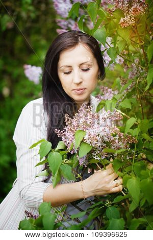 Beautiful Young Brunette  Smelling Flower