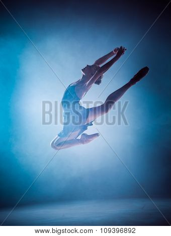 The silhouette of young ballet dancer jumping on a blue backgrou