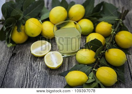 Fresh juicy lemons and a glass of homemade lemonade on a wooden background.