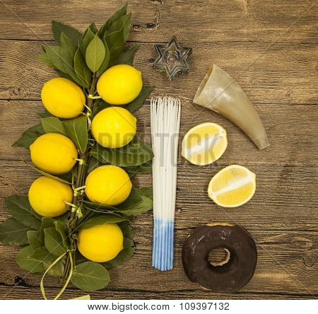 Branch lemons  donuts candles  crown of thorns and goat horn. Symbols of the great holiday of Hanukkah. On wooden background