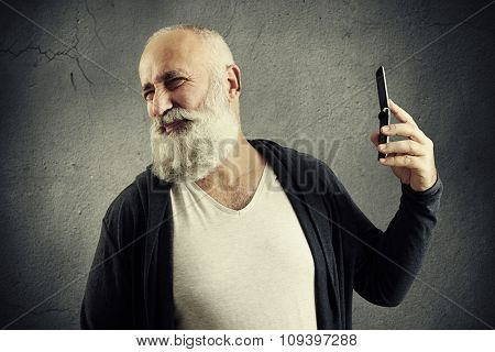 bearded senior man turning aside from his cellphone over dark wall